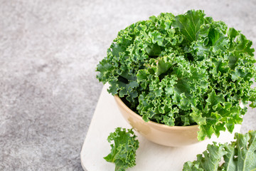 Bowl of curly green Kale on grey background with copy space
