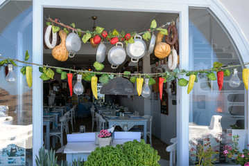 TRaditional Greek tavern decorated with different vegetables and cooking pans.