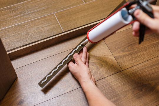 Home Door Installation. Worker use a metal profile to close the corner seam on the floor. Man putting glue on a metal profile.