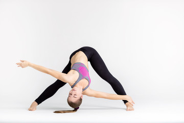 Young sportwoman stretching muscles on white background
