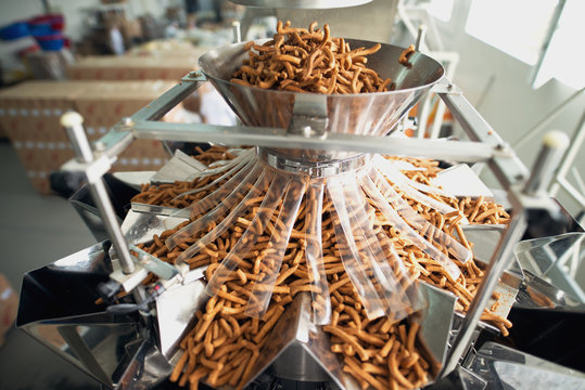 Closeup of salty snacks in food factor production line.