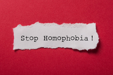 closeup of white torn paper on red paper background - Stop Homophobia !