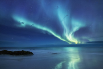 Foto auf Acrylglas Nordlicht Aurora borealis on the Lofoten islands, Norway. Green northern lights above ocean. Night sky with polar lights. Night winter landscape with aurora and reflection on the water surface.