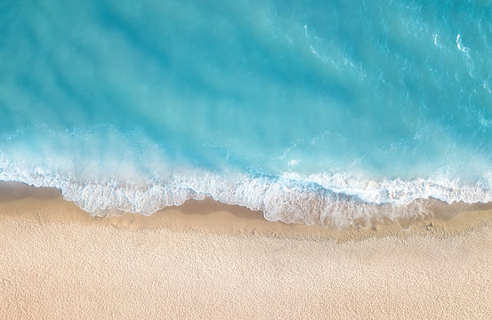 Beach and waves from top view. Aerial view of luxury resting at sunny day. Summer seascape from air. Top view from drone. Travel concept and idea