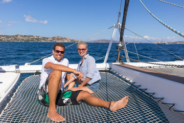 Romantic couple relaxing on a summer vacations sailin cruise, sitting on a luxury catamaran, sailing in Maddalena Archipelago, Sardinia, Italy.