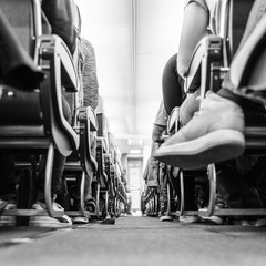 Low agle view of passenegers commercial airplane aisle with passenegers sitting on their seats while flying. Black and white image.