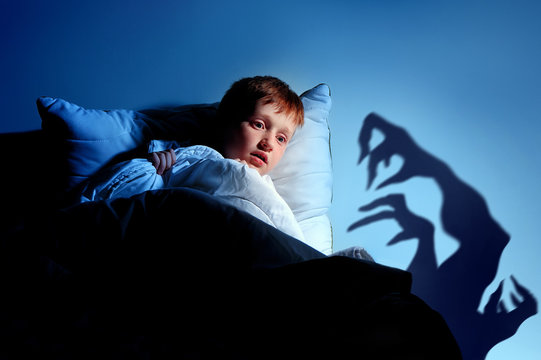 Little red haired  boy imagining monsters under the bed