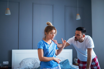 Couple having argue in their bedroom. Both of them are angry and ready to fight.
