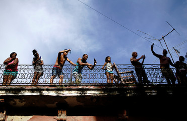 People watch the annual procession of Our Lady of Charity, the patron saint of Cuba, on the streets of downtown Havana