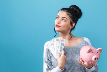 Young woman holding a piggy bank with us dollar bills