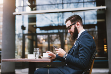 Businessman outside taking break at coffee shop.