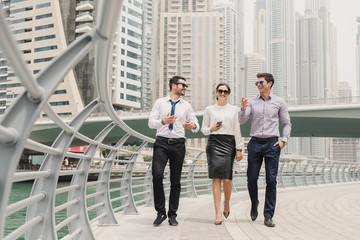 Modern young businesspeople in suit in Dubai Marina walking to their office and talking about new marketing moves and ideas.