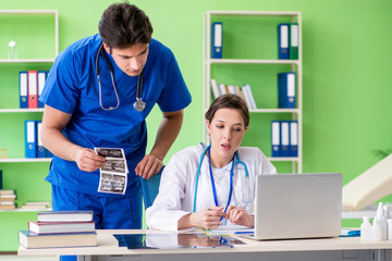 Woman and man gynecologists discussing medical case at the clini