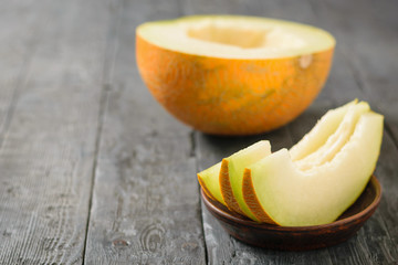 Ripe melon pieces on a clay bowl and half a melon on a wooden table.