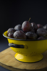 Fresh plums in yellow colander
