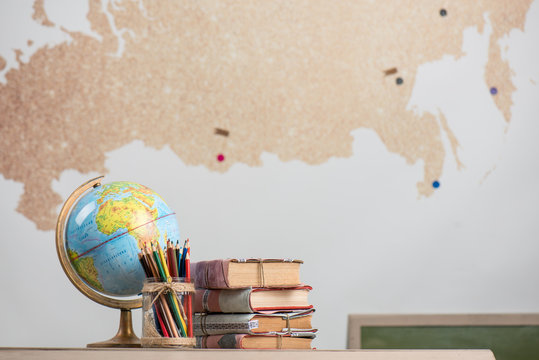 School background, books, globe and color pencils are on the desk