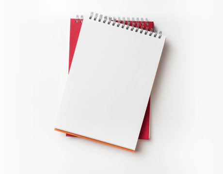 Top view of red spiral notebook and pencil