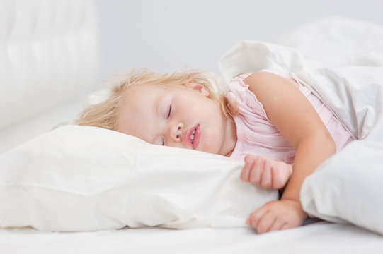 little baby girl sleeping on a bed