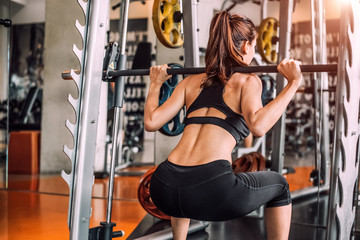 Beautiful sporty sexy woman doing squat workout in fitness gym workout training center sport club. bodybuilding muscular strength and power exercise acitivity. People and lifestyle concept. Rear view
