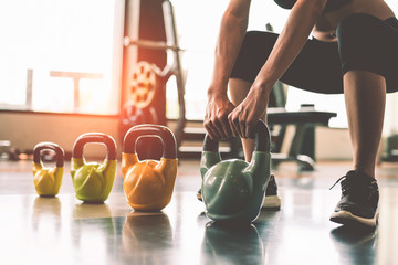 Close up of woman lifting kettlebell like dumbbells in fitness sport club gym training center with sport equipment near window background. Lifestyles and workout exercise for bodybuilding and healthy Fototapete