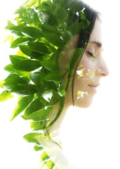 Double exposure profile portrait of a naturally beautiful woman with closed eyes and bright green tropical leaves