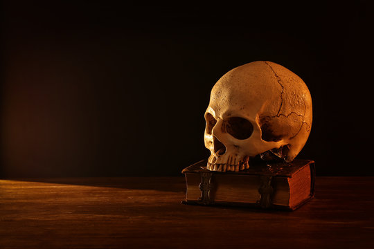 Human skull and old book over old wooden table and dark background.