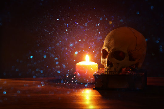 Human skull, old book and burning candle over old wooden table and darl background.
