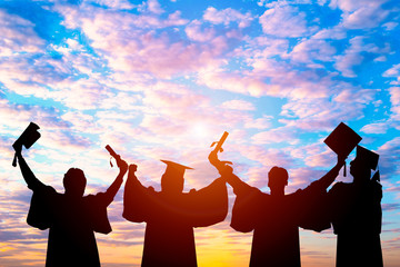 Silhouette of Student Graduation. They are seeing sunset. They are standing and show hand.They are celebration in Graduate , Education,academic, Photo concept Silhouette and Success