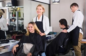 Positive aged woman cutting girl hair