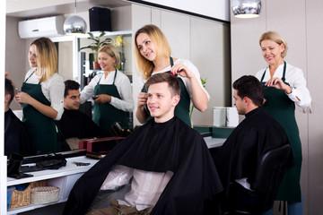 Positive blonde hairdresser serving teenager