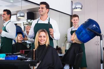 Positive young man cutting long hair of girl