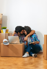 Happy young couple moving into their new home. They sitting on the floor and choosing colors for the walls.