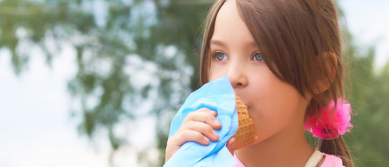 Pretty little girl eating licking big ice cream in waffles cone happy laughing on nature background