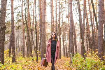 Season, nature and people concept - Woman in autumn park posing with suitcase