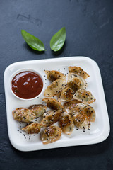 Fried korean wontons with sesame seeds and dipping sauce on a white plate, vertical shot on a black stone background