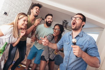 Group of friends playing karaoke at home. Concept about friendship, home entertainment and people
