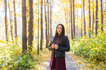 Season, fall and people concept - beautiful young woman walking in autumn park
