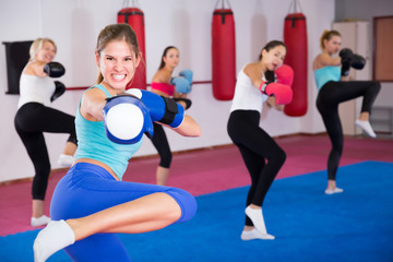 Group of happy female are doing kick in gym