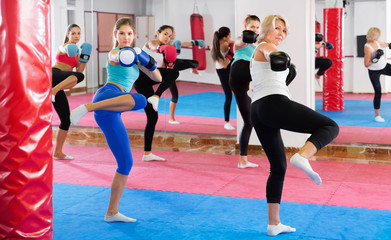 Sporty women are training box in gym.