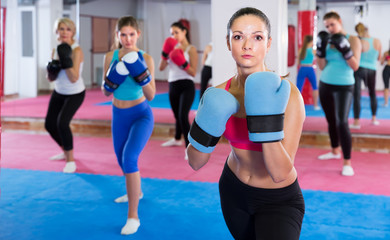 Portrait of young girl who is boxing with group in gym