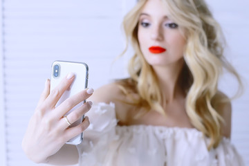selfie make-up blonde / make-up model makes selfie on phone, concept style glamor fashion, make-up