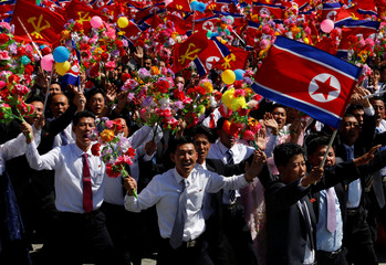 People wave plastic flowers and flags during a military parade marking the 70th anniversary of North Korea's foundation in Pyongyang