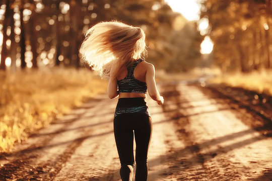 autumn adult girl running sport / beautiful active girl adult running and practicing outdoor sports in the autumn season