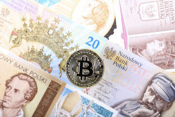 Bitcoin coin on the background of Polish banknotes