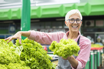 Senior woman sells lettuce on marketplace