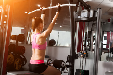 slim woman wearing pink and black professional sportswear pumping an iron barbell at the gym. Strength and motivation concept