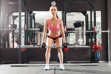 girl with a ponytale wearing pink and black professional sportswear squatting with an iron barbell at the highly equipped gym. Strength and motivation concept