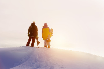 Two snowboarders looks at sunset in mountains