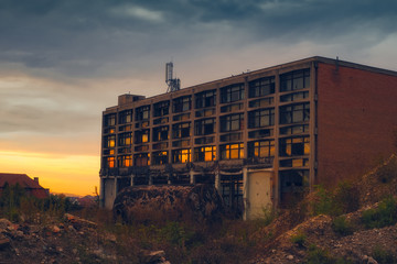 sunset reflected in the broken windows of the abandoned industrial building