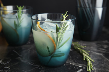 Tasty refreshing pear cocktail with rosemary on table